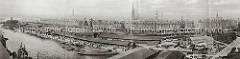 Historisches Panorama vom Grasbrookhafen; Binnenschiffe und Schuten liegen am Dalmannkai vor den offenene Lagerschuppen, in denen die Waren gestapelt sind. Auf der Landseite stehen auf den Schienen der Hafenbahn die Güterwaggons.
