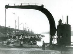 Blick vom Ende des Grasbrookhafens unter einen Kranausleger zum Hübenerkai; Dampffrachter und Oberländer Kähne liegen dicht in dem Hamburger Hafenbecken.