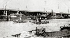 Dampffrachter liegen am Dalmannkai des Grasbrookhafens; aus den hohen Schornsteinen steigt leichter Qualm. Ein Hafenschlepper schleppt eine leere Schute -  im Vordergrund stösst ein Ewerführer seine Schute mit dem Peekaken vom Nachbarschiff ab.