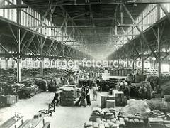 Innenansicht eines Lagerschuppens im Hamburger Hafen / Hansahafen, O'Swaldkai. Hoher luftiger Lagerraum, Holzkonstruktion - Lagerarbeiter mit Sackkarre, Stechkarre.