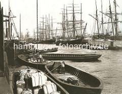 Schuten werden am Kirchenpauerkai beladen  - ein Kran bringt Kisten an Bord des Lastkahns; Ewerführer bugsieren ihre Boote mit Bootshaken.