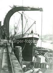 Dampfkran am Dalmannkai im Hamburger Grasbrookhafen - der Hafenkran setzt Kisten mit schwedischen Zündhölzern in der Schute ab. Geschichte der Hafenarbeit im Hamburger Hafen.