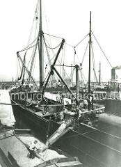 Alte Fotografie, Hafenarbeit im Hamburger Hafen - die Ladung eines Getreidefrachters wird gelöscht; die Schiffswinde bringt das Getreide in Körben hoch, über eine Schüttrinne wird es in einen offenen Kahn transportiert.