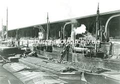 Ein Dampfer bunkert am Dalmannkai im Hamburger Hafen Kohle; Kohlenträger tragen Kiepen mit Kohle über eine Leiter von der beladenen Schute auf das Dampfschiff im Grasbrookhafen.