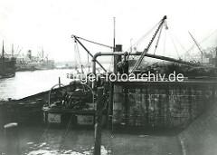 Kuhwärder Hafen / Steinwerder Ufer - historische Hafenbilder aus Hamburg; ein Schutensauger entnimmt einer Schute Baggergut und transportiert es an Land.