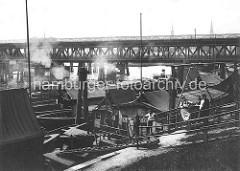 Stadtdeich im Hamburger Oberhafen / - Kanal, Persenninge werden gewaschen und imprägniert; Oberhafenbrücke - zweistöckige Strassenbrücke / Eisenbahnbrücke über den Oberhafenkanal.