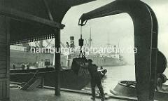 Alte Aufnahme aus dem Baakenhafen im Hamburger Hafen - eine Kiste wird von einem Hafenarbeiter mit einem Kran auf den Kai gehievt - im Hintergrund Frachtschiffe am Petersenkai. ( ca. 1905 )