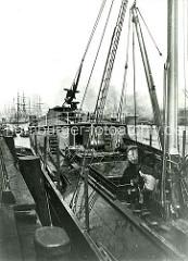 Historische Fotos aus dem Hafen Hamburgs; Spiritusfässer werden im Hansahafen über eine Schiffswinde in ein Hafenfahrzeug gelöscht.