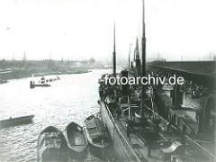 Blick über den Grasbrookhafen; lks. der Hübenerkai, re. der Dalmannkai - Schuten und Kähne liegen längsseits eines Frachtschiffs - Kräne am Kai transportieren die Fracht; offene Schuppen mit Kisten und Ballen.
