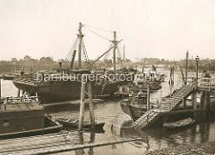 Klütjenfelder Hafen, Hamburger Hafenbecken zwischen dem Spreehafen und dem Reiherstieg - Historische Aufnahme; Frachtschiffe / Arbeitsschiffe an der Wassertreppe.