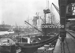 Historische Aufnahme von der Arbeit im Hamburger Hafen - Schuten, Dampfer und Getreideheber im Kaiser-Wilhelm-Hafen.