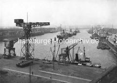Alte Fotografie aus dem Hafen Hamburgs - Blick über den Kaiser-Wilhelm-Hafen - Hafenkräne, Schiffe an den Kaianlagen und Dalben in der Mitte des Hafenbeckens.