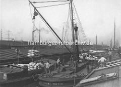 Melniker Ufer im Moldauhafen; Hafenbecken im Hamburger Hafen - eine Dampfwindenschute verlädt Korn in Säcken von einem Oberländer Kahn auf eine Kastenschute.