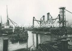 Altes Foto aus dem Hafen Hamburgs - Kuhwärder Hafen in Hamburg Steinwerder.  Getreideheber und Getreidesilo der Fa. Henry P. Newman - Schuten und Oberländer Kahn; ein Schwimmkran lädt Schwergut auf einen Frachter.