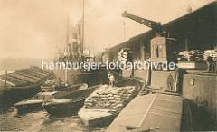 Historisches Bild von der Arbeit im Hambuger Hafen - eine Hieve Säcke hängt an einem Rollkran am Dalmannkai im Grasbrookhafen; Schuten und Binnenschiffe haben am Kai und längsseits an einem Frachtdampfer festgemacht. ( ca. 1910 )