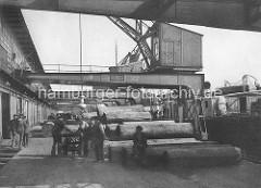 Hafenarbeiter am Mönckebergkai im Hamburger Ellerholzhafen; Baumstämme zur Verladung auf dem Kai; Hafenkräne.