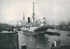 Dampfschiff, Frachtschiff am Grevenhofer Ufer im Kuhwärder Hafen. Der Frachter liegt im Hafenbecken, die Ladung wird auf die längsseits liegenden Flussschiffe, Binnenschiffe gelöscht. Alte Fotografien aus dem Hamburger Hafen.