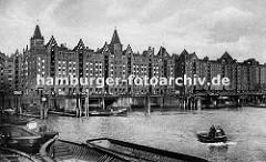 Blick über den Brooktorhafen zu den Speicherblöcken V + X. Schuten und Kähne liegen an der Kaimauer oder den Holz Duckdalben. Eine kleine Barkasse fährt durch das Hamburger Hafenbecken Richtung Magdeburger Hafen.