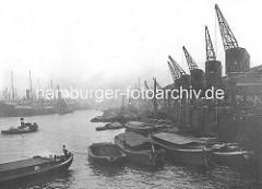 Kaiser Wilhelm Hafen / Auguste Viktoria Kai; Schuten und Kähne am Hafenkai; ein Ewerführer steuert seine Schute mit einem Peekhaken. Alte Fotografien aus dem Hafen Hamburgs.