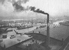 Blick auf den Kuhwerder Hafen - Dampfer und Segelschiffe liegen an Dalben im Strom und werden über Schuten und Binnenschiffe be- und entladen. Im Vordergrund der qualmende Schornstein der Hamburg Indischen Reiswerken am Steinwärder Ufer.