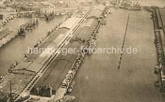 Historisches Flugbild vom Kaiser Wilhelm Hafen - Lagerschuppen am  Auguste Viktoria Kai, lks. davon der Kuhwerder Hafen und die Kaischuppen am Grevenhofer Ufer; im Hintergrund die Grevenhofer Schleuse.