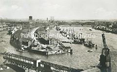 Blick auf die Norderelbe zu den Elbbrücken - Frachtschiffe liegen an Dalben vor dem Kirchepauerkai; Lks. die Lagerschuppen am Petersenkai im Baakenhafen.