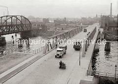 Blick über den Reiherstieg vom Kleinen Grasbrook nach Steinwerder; mit Fässern beladene Lastwagen, Fahrradfahrer und ein Motorrad mit Beiwagen überqueren die Reiherstiegbrücke. Links die Eisenbahnbrücke über den Reiherstieg.