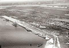Luftbild von der Baustelle im Waltershofer Hafen; die Kaianlage des Burchardkais ist halb fertig gestellt. Arbeitsschuten liegen an der Spundwand, ein schwimmendes Förderband bringt den Sand von den Schuten zum Verfüllen auf den Kai - ein Kettenb