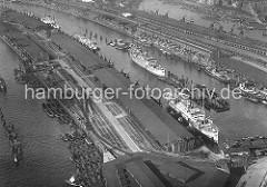 Luftaufnahme vom Baakenhafen und Norderelbe. Schuten liegen am Kirchenpauerkai; die Lastkähne werden mit Kohle beladen - auf dem Kai umfangreiche Gleisanlagen der Hafenbahn. Am Petersenkai des Baakenhafens liegen Frachtschiffe, die dort be- und e