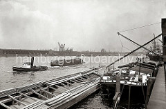 Binnenschiffe liegen am Holthusenkai in der Norderelbe - über ein Rohr wird eines der Lastschiffe mit Schüttgut befüllt; Schlepper ziehen Transportschiffe Richtung Hafen. Am Kirchenpauerkai liegt Kohlenheber und mehrere Schiffe an den Dalben i