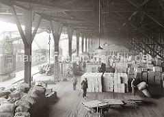 Die unterschiedlichsten Waren sind im Lagerschuppen 14 des Dalmankais im Grasbrookhafen gestapelt. An einem der Kaikrane, die von Laufschienen entlang der Kaimauer geführt werden hängt eine Ladung Kisten, die auf der Laderampe abgesetzt wird.