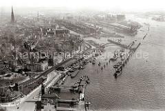 historisches Luftbild von Hamburg; im Vordergrund lks. das St. Pauli Fährhaus und die U-Bahnstation Landungsbrücken. Am Hafentor / Vorsetzen die Speicherschuppen und Krane einer Rheinschifffahrtslinie.