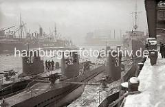 Drei U-Boote liegen nebeneinander am Versmannkai vor den Fruchtschuppen des Baakenhafens; der Kai ist mit Schnee bedeckt. Im Hintergrund ist das Gasometer beim Magdeburger Hafen zu erkennen.