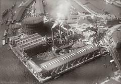 Luftfoto vom Gaswerk auf dem Grossen Grasbrook; im Bildzentrum Halden der Kohle, die zur Energiegewinnung verwendet wurde, davor ein Fruchtschuppen mit Kranen am Magdeburger Hafenbecken. Lks. oben die Kaianlage der Gaswerke und Lagerschuppen.