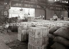 Blick in den Lagerschuppen 15 am Dalmannkai - Holzkisten und Säcke sind in dem Lagerraum gestapelt - Hafenarbeiter schieben leere Sackkarren zur Laderampe. Links weist ein Schild auf Verletzungsgefahr hin, die durch Ballen mit Bandeisen und Draht