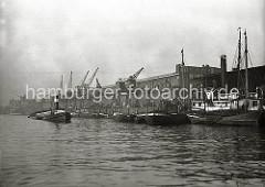 Ein Schlepper mit hohem Schornstein schleppt eine Schute durch das Hafenbecken des Baakenhafens; weitere Schuten und Binnenschiffe liegen vor den Fruchtschuppen am Versmannkai. Rechts ein Ausschnitt des offenen Kaischuppens 25, der am  östlichen