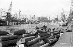 Blick über den Baakenhafen 1956; am Versmannkai liegen Schuten mit Baumstämmen beladen - ein Frachter hat an den Eisenpollern festgemacht. In der Mitte des Hafenbeckens liegen weitere Frachtschiffe an Dalben - ein Schwimmkran löscht die Ladung; im