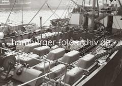Blick auf einen Frachter am Dalmannkai des Grasbrookhafens; an Deck des Frachtschiffs sind Badewannen gestapelt und aus dem Laderaum werden große Holzkisten mit dem Kran herausgehoben. Im Hafenbecken liegen mit Kisten beladene Schuten längsseits.