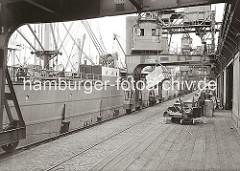 Eine Ladung Kisten hängt am Kranhaken des Hafenkrans, dessen Halbportal die Kaianlage und Laderampe des Dalmannkais vom Hamburger Grasbrookhafen überspannt. Der Kranführer sitzt oben in dem Führerhaus, das rundherum verglast ist.
