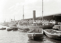 Die Ladung eines britischen Frachtschiffs wird am Dalmannkai des Hamburger Grasbrookhafens gelöscht. Über schiffseigene Ladebäume werden Säcke in die längsseits liegenden Schute verladen. Ein weiterer Lastkahn ist mit Kisten hoch beladen.