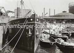 Der britische Frachter AUK liegt am Dalmannkai des Hamburger Grasbrookhafens. Hafenkrane löschen die Ladung des Frachtschiffs - auf der Wasserseite wird über einen bordeigenen Ladebaum eine Hieve Kartons auf eine längsseits liegende Schute geladen
