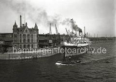 Blick über den Magdeburger Hafen zum Versmannkai des Hamburger Baakenhafens. Der Dampfer NATIA hat am Kai fest gemacht -  Qualm steigt aus seinem Schornstein. Auf der Kaianlage transportieren Kaiarbeiter Fruchtkisten mit der Sackkarre in den Fru