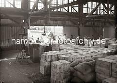 Die Ladung eines Frachters wird am Dalmannkai des Hamburger Grasbrookhafens gelöscht - eine Hieve Säcke wird gerade auf der Laderampe abgesetzt. Ein Lagerarbeiter zieht eine Sackkarre schwer mit Säcken beladen in den Kaischuppen.