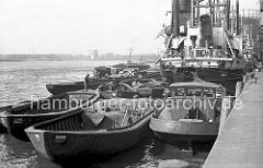 Der Frachter GEIER hat am Versmannkai im Baakenhafen fest gemacht; seine Heckleinen sind um den Poller am Kai gelegt. Über Schuten, die um das Frachtschiff herum liegen, werden die Güter gelöscht oder neue Ware an Bord geladen. Auf eine der Schuten