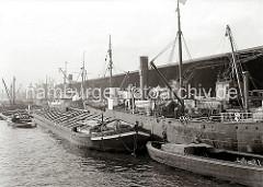 Arbeit im Hamburger Hafen - die Ladung der Schiffe wird gelöscht und neue Fracht wird mit den Hafenkranen und schiffseigenen Ladebäumen an Bord gebracht. Die Güter kommen von der Landseite aus den Kaischuppen des Dalmannkais.