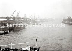 Der Baakenhafen im Nebel - Frachtschiffe liegen am Versmannkai, Schuten und Binnenschiffe  haben für eine Außenbordbeladung längsseits fest gemacht.