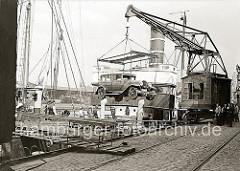 Verladung eines Autos am Hübenerkai des Grasbrookhafens -  die Hafenarbeiter stehen neben dem Kran und an Deck des Frachtschiff; sie beobachten, wie das Kraftfahrzeug an Bord des Frachter gehievt wird.