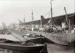 Güterumschlag am Dalmannkai des Grasbrookhafens; die Frachtschiffe liegen dicht an dicht an der Kaimauer und werden über die Hafenkrane be- und entladen. In der Bildmitte ist das Motorschiff HOLSTENAU zu erkennen.