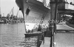 Der Frachter SCHAUENBURG liegt am Petersenkai im Baakenhafen; Matrosen des Frachtschiffs stehen auf einem Arbeitskahn und streichen den Bug des Schiffs mit Rostschutzfarbe. Im Vordergrund eine eiserne Leiter an der Kaimauer, die zum Besteigen der Kä