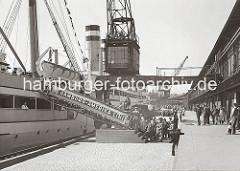 Am Versmannkai besteigen Passagiere die Gangway eines Passagierschiffs der Hamburg-Amerika-Linie HAPAG. Unter dem Halbportalkran stehen die LKW mit dem Gepäck der Amerikareisenden, ein Arbeiter wartet darauf, die Koffer an Bord des Dampfers trag